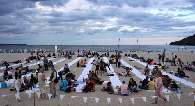 """За седма поредна година """"Най-дългата вечеря на плажа"""" събра вчера стотици привърженици на идеята на Аспаруховския плаж, пишат от Kmeta.bg. Условието бе..."""